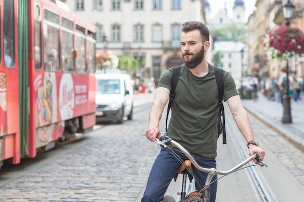 Homem, bicicleta equitação, ligado, rua Foto gratuita