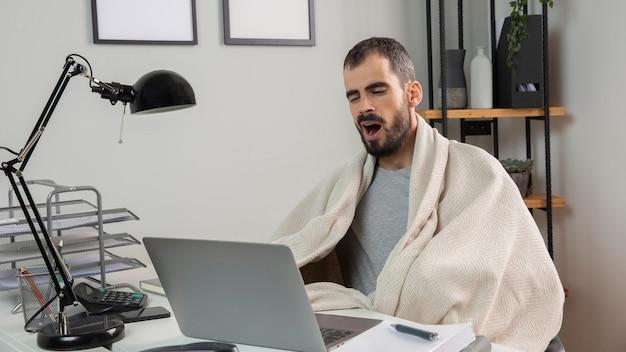Homem bocejando enquanto trabalha em casa Foto Premium