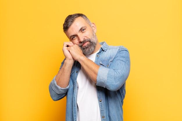 Homem bonito adulto apaixonado e bonito, adorável e feliz, sorrindo romanticamente com as mãos ao lado do rosto Foto Premium
