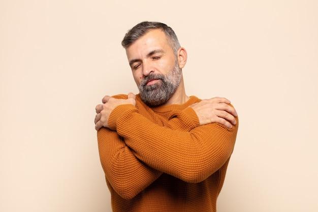 Homem bonito adulto se sentindo apaixonado, sorrindo, se abraçando e se abraçando, permanecendo solteiro, sendo egoísta e egocêntrico Foto Premium