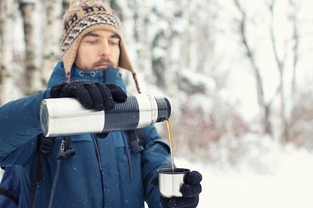 Homem bonito alpinista em roupas quentes derrama chá em caneca de garrafa térmica na floresta de inverno. Foto Premium
