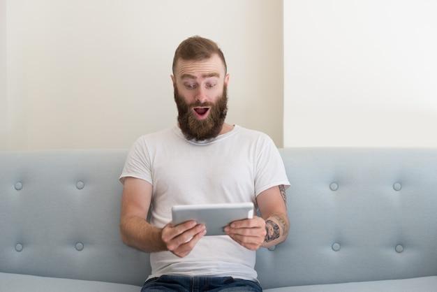 Homem bonito animado com tatuagem assistindo vídeo no tablet Foto gratuita