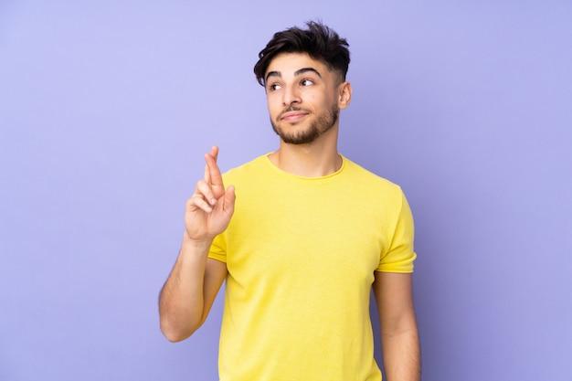 Homem bonito árabe sobre parede com dedos cruzando e desejando o melhor Foto Premium
