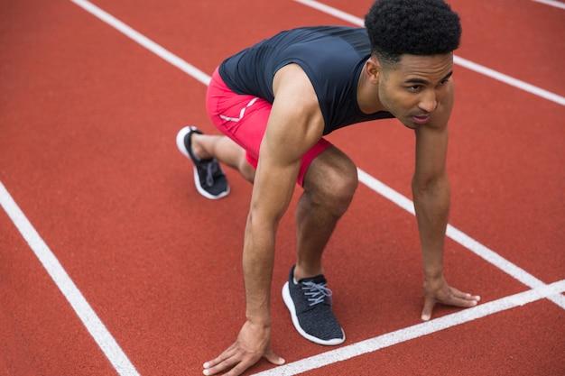 Homem bonito atleta africano concentrado pronto para começar Foto gratuita
