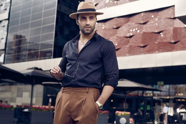 Homem bonito bronzeado hipster muscular brutal posando nas ruas Foto Premium