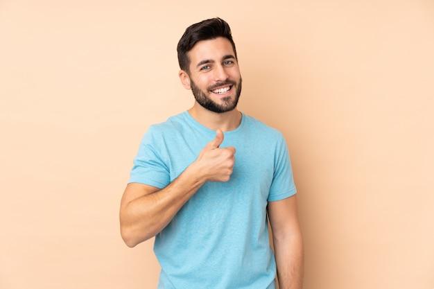 Homem bonito caucasiano isolado na parede bege, dando um polegar para cima gesto Foto Premium