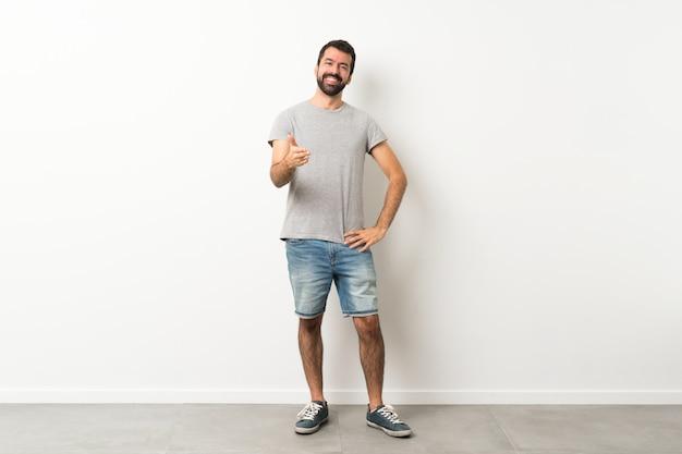 Homem bonito com barba, apertando as mãos Foto Premium