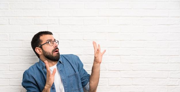 Homem bonito com barba sobre a parede de tijolo branco nervoso e com medo Foto Premium