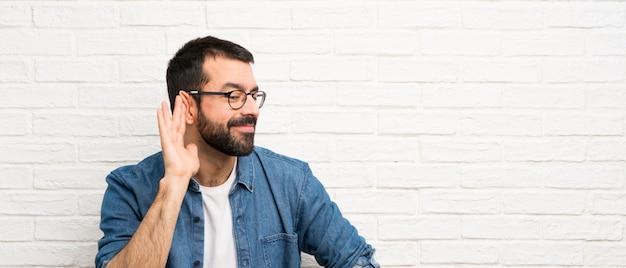 Homem bonito com barba sobre parede de tijolos brancos ouvir algo, colocando a mão sobre a orelha Foto Premium