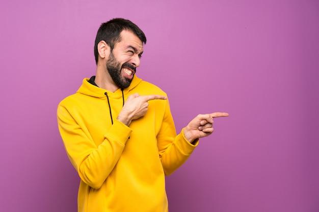 Homem bonito com moletom amarelo assustado e apontando para o lado Foto Premium