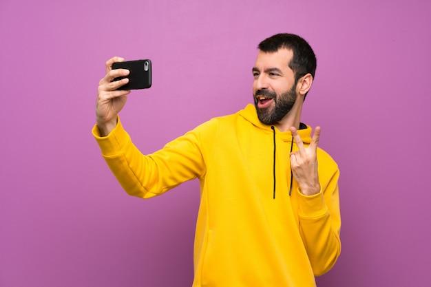 Homem bonito com moletom amarelo fazendo um selfie Foto Premium