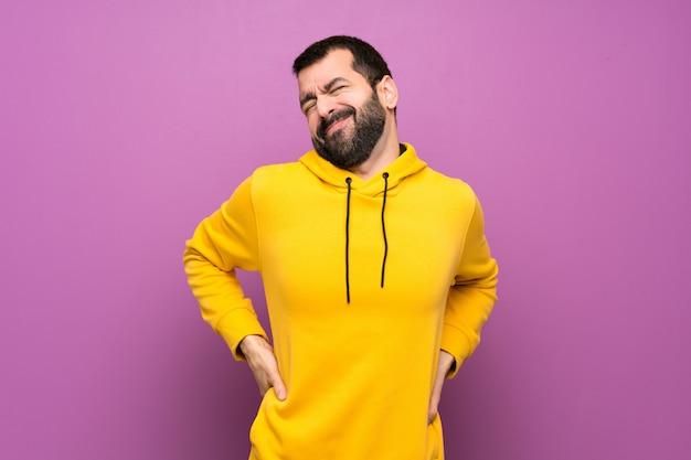 Homem bonito com moletom amarelo, sofrendo de dor nas costas por ter feito um esforço Foto Premium