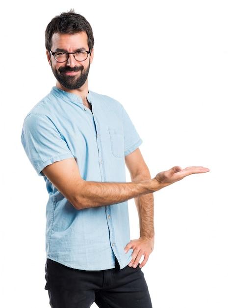 Homem bonito com óculos azuis apresentando algo Foto gratuita