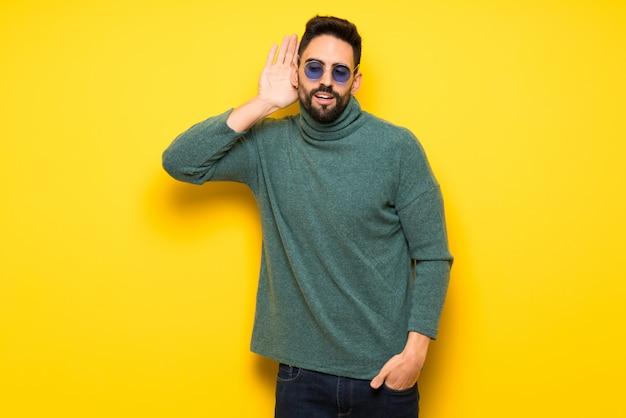 Homem bonito com óculos de sol, ouvindo algo, colocando a mão na orelha Foto Premium