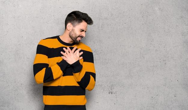 Homem bonito com suéter listrado, tendo uma dor no coração sobre a parede texturizada Foto Premium