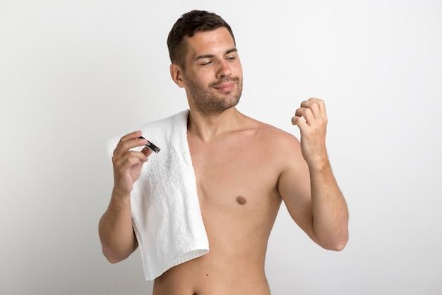 Homem bonito com toalha e olhando as unhas, mantendo a unha clipper Foto gratuita