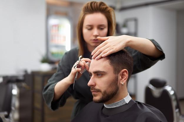 Homem bonito de olhos azuis sentado na barbearia. mulher de cabeleireiro hairstylist cortando o cabelo dele. barbeiro feminino. Foto Premium