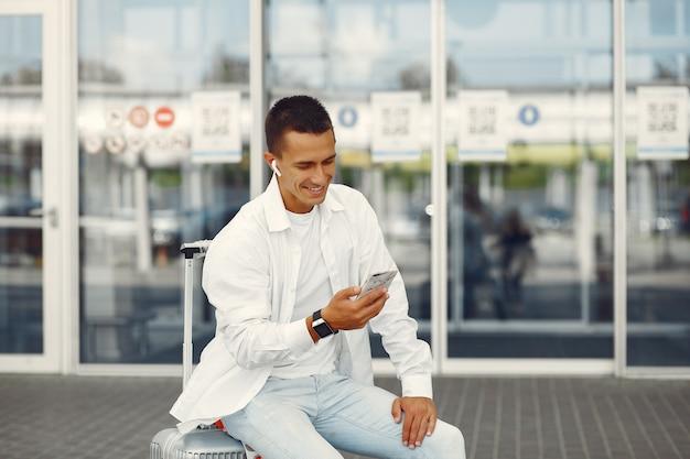 Homem bonito, de pé perto do aeroporto Foto gratuita