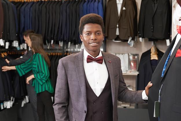Homem bonito de terno posando na boutique. Foto gratuita