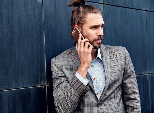 Homem bonito de terno xadrez cinza, falando com o smartphone Foto gratuita