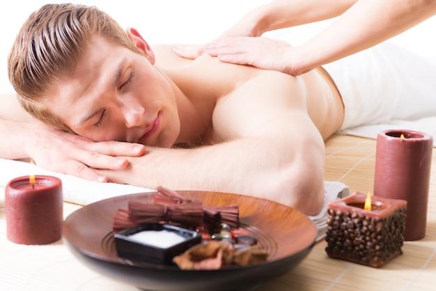 Homem bonito, deitado em um salão de spa, desfrutando de uma massagem profunda nas costas. Foto gratuita