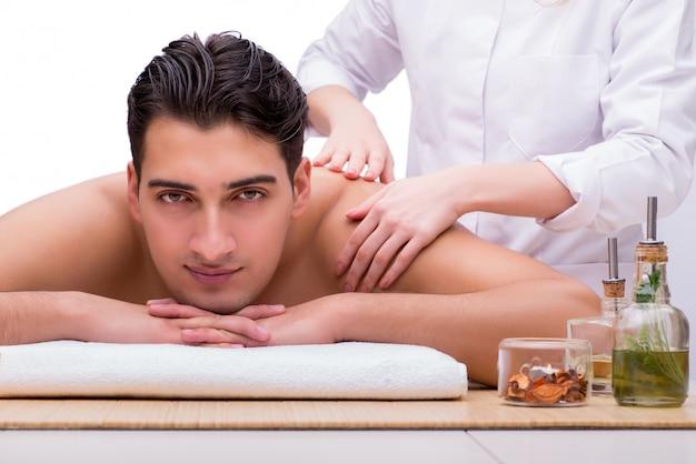 Homem bonito durante o spa massageando a sessão Foto Premium