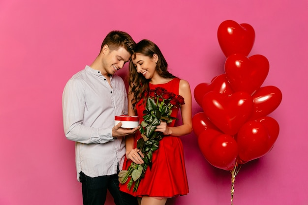 Homem bonito e mulher atraente olhando para caixa com presente, rosas vermelhas Foto gratuita