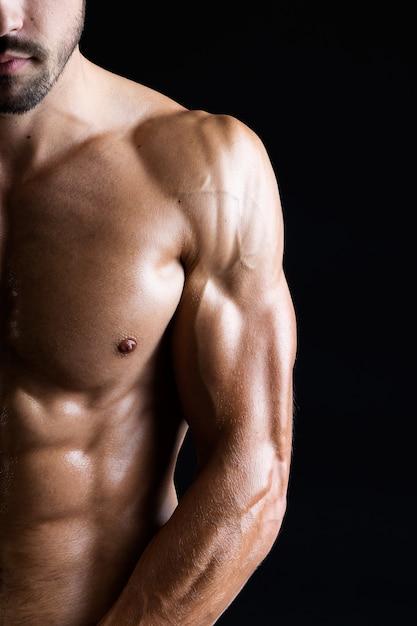 Homem bonito e musculoso em fundo escuro. Foto Premium