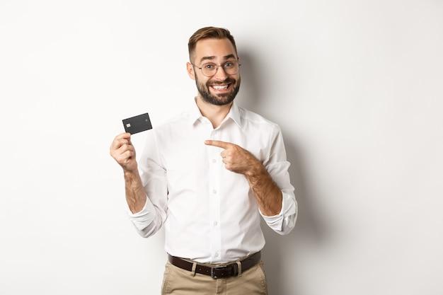 Homem bonito e satisfeito de óculos apontando para o cartão de crédito, satisfeito com os serviços bancários, em pé Foto gratuita