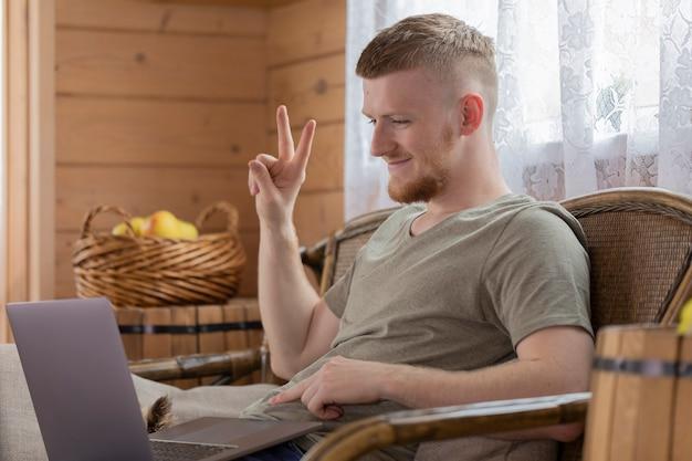 Homem bonito e sorridente se comunica com os pais na internet usando um laptop Foto Premium