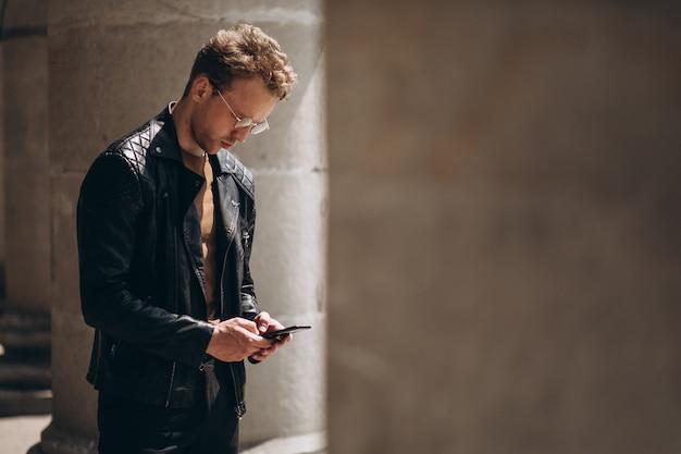 Homem bonito em espetáculos usando telefone Foto gratuita