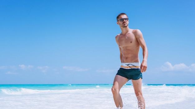 Homem bonito em férias pelo oceano Foto gratuita