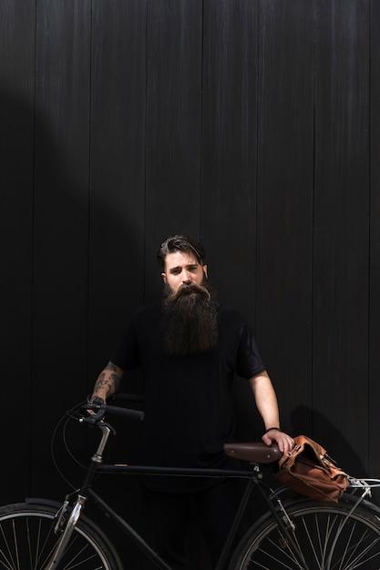 Homem bonito em pé com a bicicleta e bolsa de ombro contra o pano de fundo preto escuro Foto gratuita