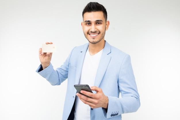 Homem bonito em um casaco azul com um cartão de crédito com uma maquete e um telefone na mão em um fundo branco studio Foto Premium