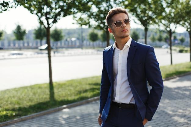 Homem bonito em um terno de negócio caminha ao longo da rua em um dia ensolarado Foto gratuita