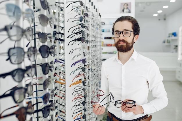 Homem bonito em uma loja de óptica Foto gratuita