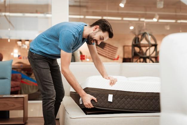 Homem bonito, escolhendo o colchão na loja de móveis Foto Premium