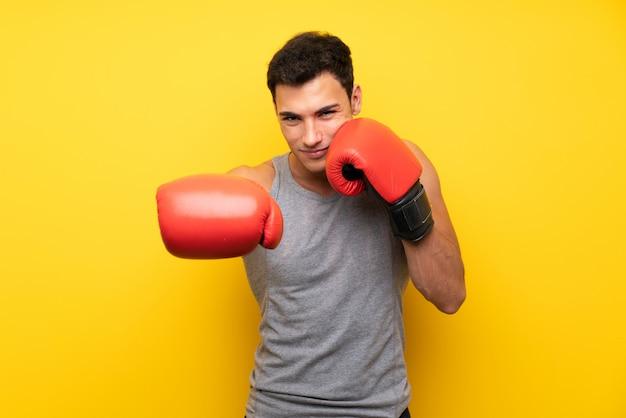 Homem bonito esporte parede isolada com luvas de boxe Foto Premium
