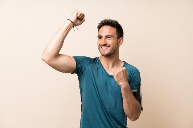 Homem bonito esporte sobre fundo isolado, celebrando uma vitória Foto Premium