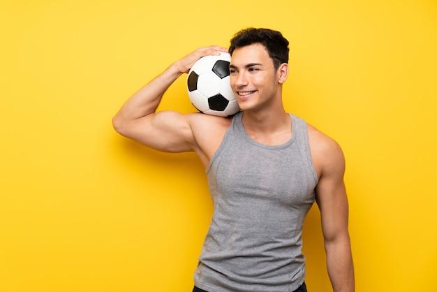 Homem bonito esporte sobre fundo isolado com uma bola de futebol Foto Premium
