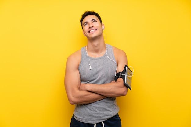 Homem bonito esporte sobre fundo isolado, olhando para cima enquanto sorrindo Foto Premium