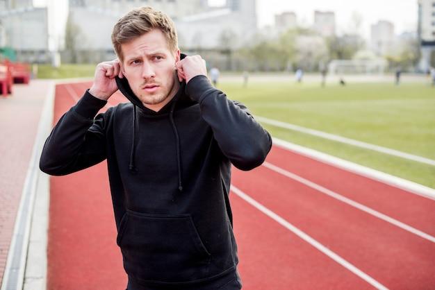 Homem bonito esporte vestindo capuz na pista de corrida Foto gratuita
