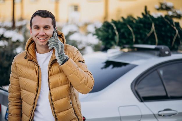 Homem bonito, falando no telefone de carro com a árvore de natal no topo Foto gratuita