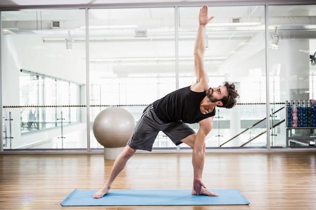 Homem bonito fazendo yoga na esteira no estúdio Foto Premium