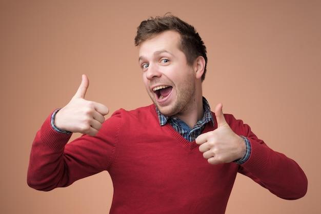 Homem bonito feliz com suéter vermelho mostrando os polegares para cima Foto Premium