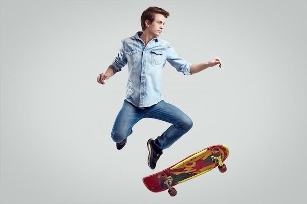 Homem bonito hipster em jaqueta jeans fazendo o flip no elegante skate Foto Premium