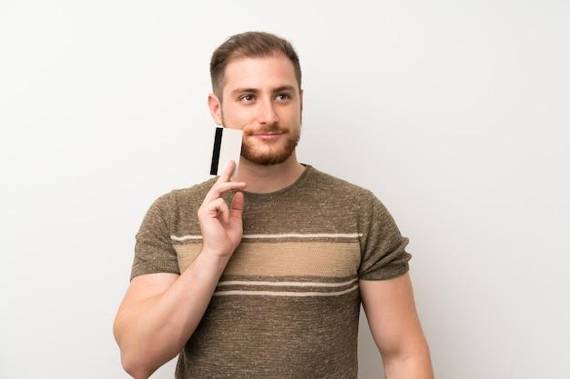 Homem bonito isolado muro branco segurando um cartão de crédito Foto Premium