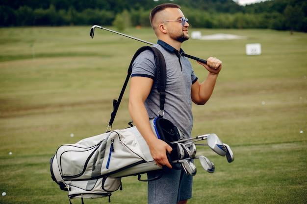 Homem bonito, jogando golfe em um campo de golfe Foto gratuita