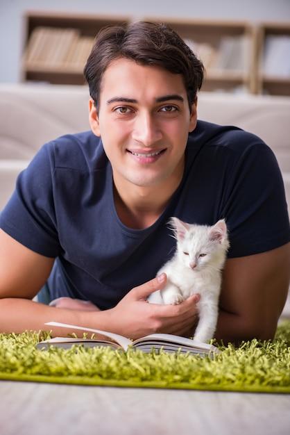 Homem bonito jovem brincando com gatinho branco Foto Premium
