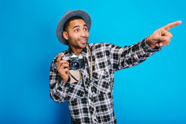 Homem bonito jovem espantado se divertindo com a câmera. viajar, curtir férias, turismo, mapa, bom humor, felicidade, emoções verdadeiras, positividade, jorney. Foto gratuita